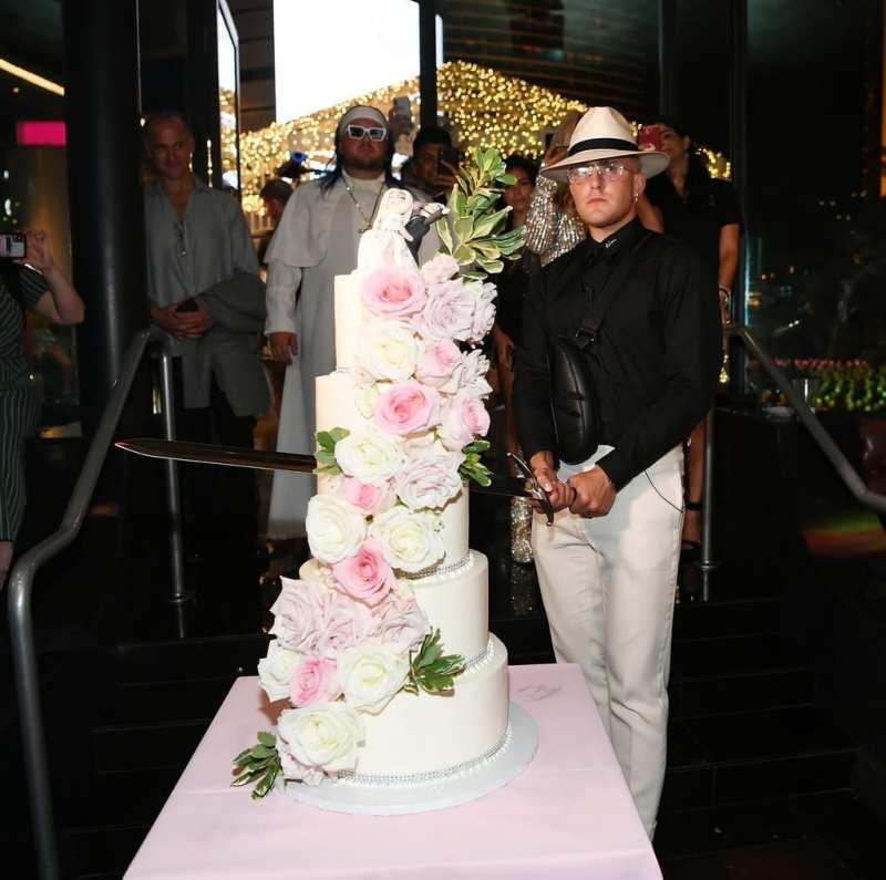 Jake Paul gets ready to slash wedding cake before having a taste.