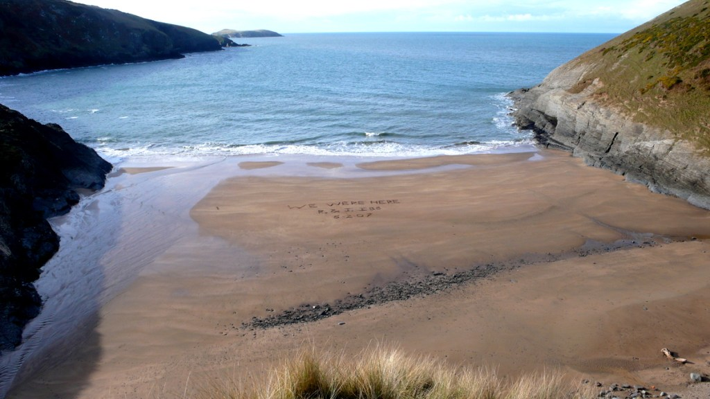 Writing in the sand at Mwnt, from a travel blog by traveljunkiegirl.com