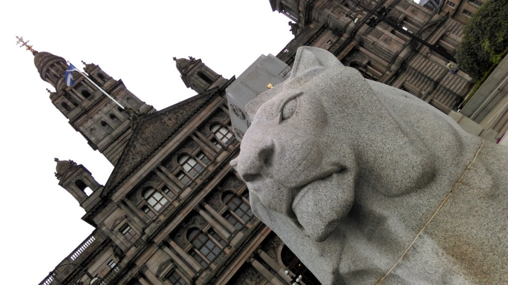 The lion in George Square, standing guard of the City Chambers building, Glasgow; from a travel blog by www.traveljunkiegirl.com
