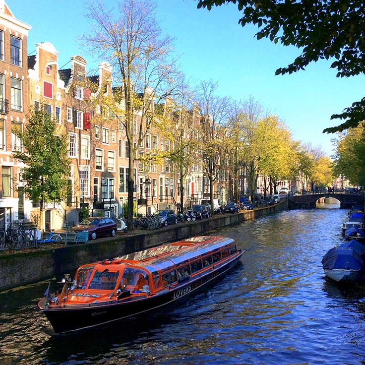Autumn in Amsterdam thins out the tree canopy so you get to see buildings normally hidden; from a travel blog by www.traveljunkiegirl.com