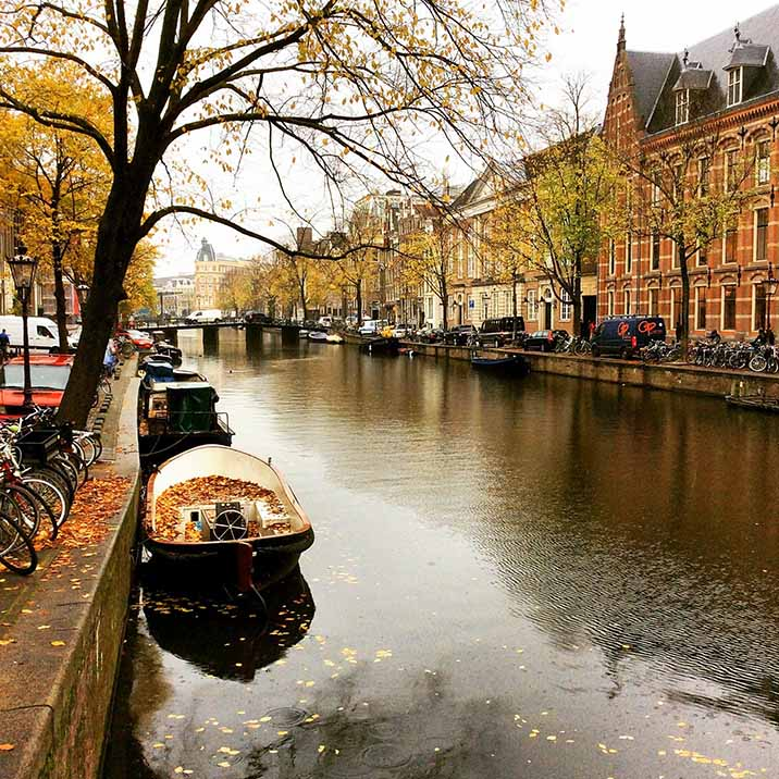 Boats fill with leaves on Amsterdam's canals in autumn; from a travel blog by www.traveljunkiegirl.com