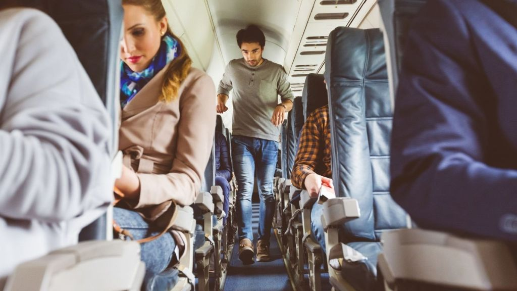 A man walks the aisle of an airplane - Tips to Conquer Jet Lag - TravelLatte
