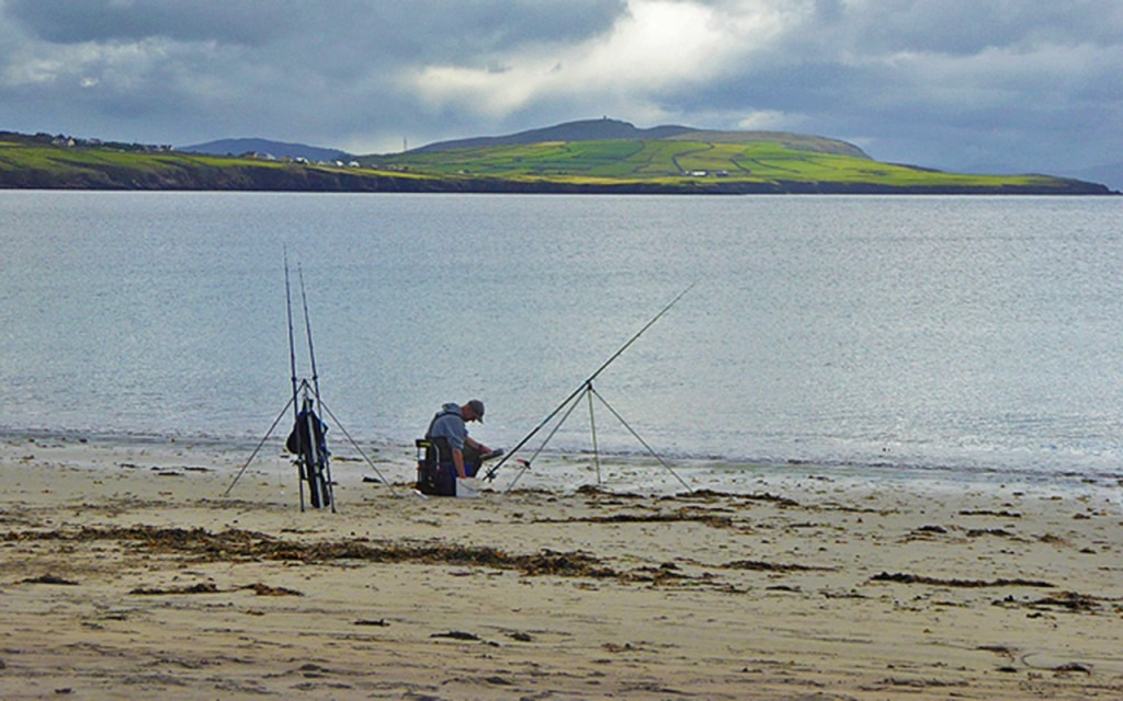 An angler on Ventry Beach on Ireland's Scenic Slea Head Drive via @TravelLatte.net