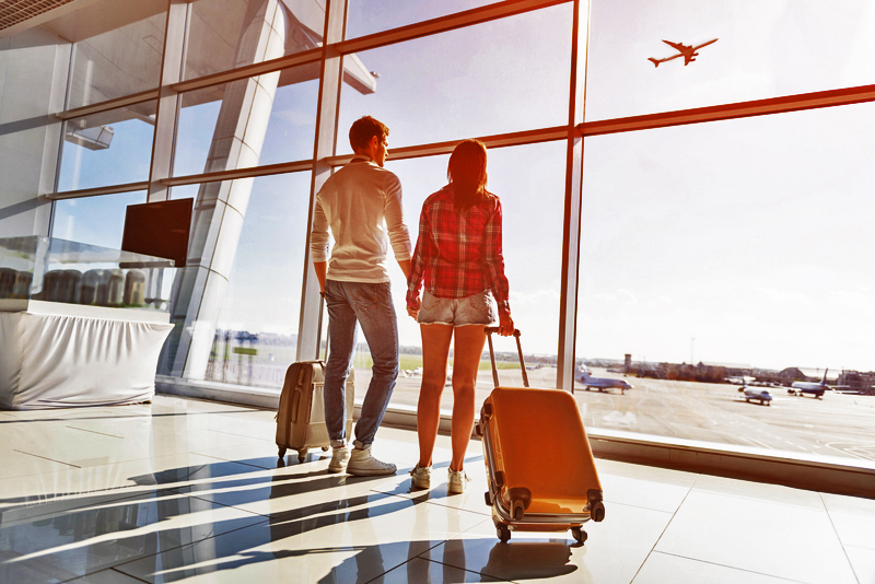 Young couple with carry-on bags - Carry-on vs Checked Luggage via @TravelLatte.net