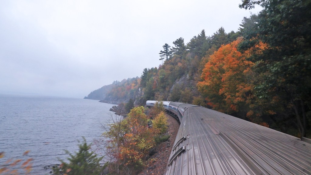 The Amtrak Adirondack between colorful trees and Lake Champlain, by TravelLatte.