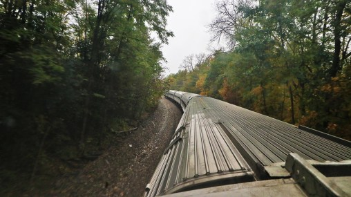 Amtrak Adirondack winding through the forest, by TravelLatte.