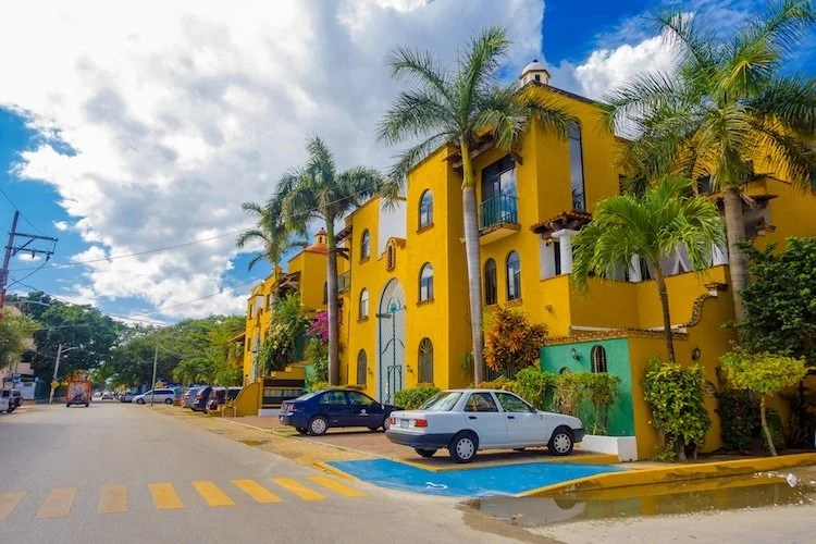 A coloful hacienda style building in Playa del Carmen, with cars parked out front and palm trees.