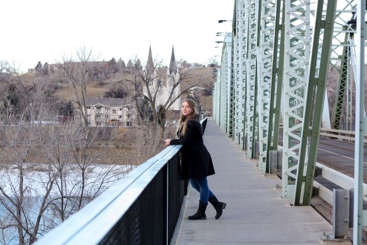 Taylor stands on a bridge with a church in the background in the city of Medicine Hat, Alberta, Canada