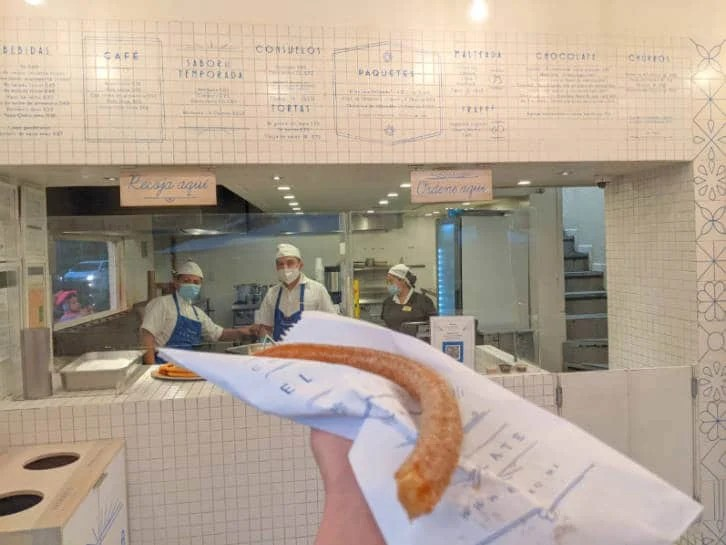 A hand holding a churro in front of Churrería El Moro