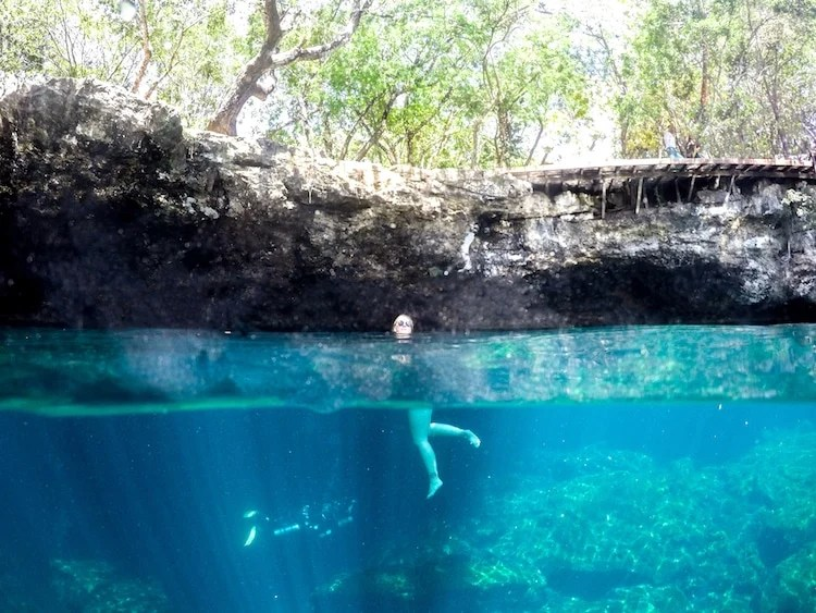 A half-underwater photo of Taylor in a cenote, with a scuba diver below.