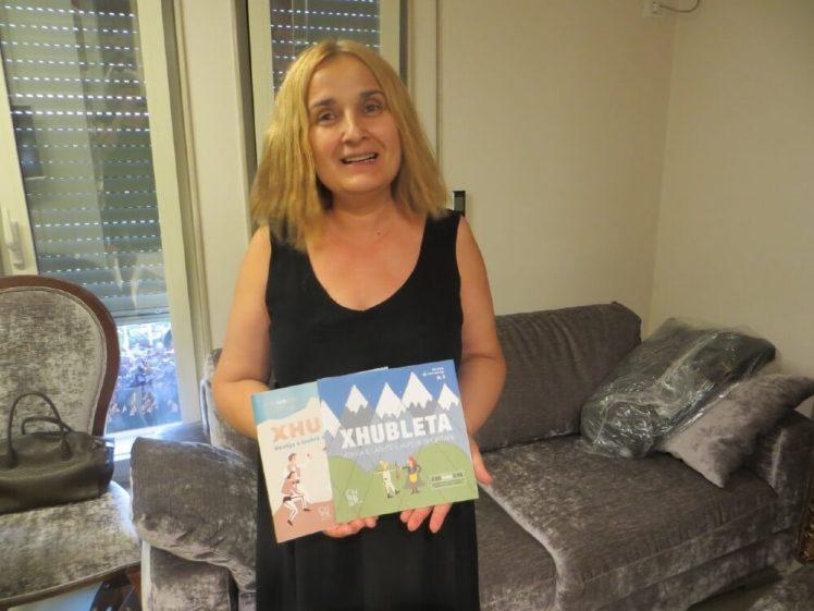 vrouw toont twee kinderboeken over klederdracht in albanie