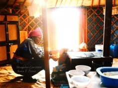 A Mongolian woman lights up the oven inside her ger