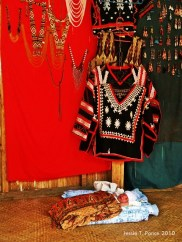A baby peacefully sleeps by a display of T'boli traditional garb and trinkets