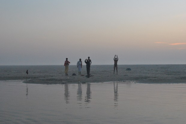 People on a sandbank in the Ganga in Varanasi before sunrise
