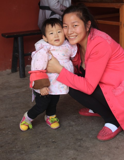 Little chinese girl and her Mom in the Yuantong Si Temple in Kunming, China