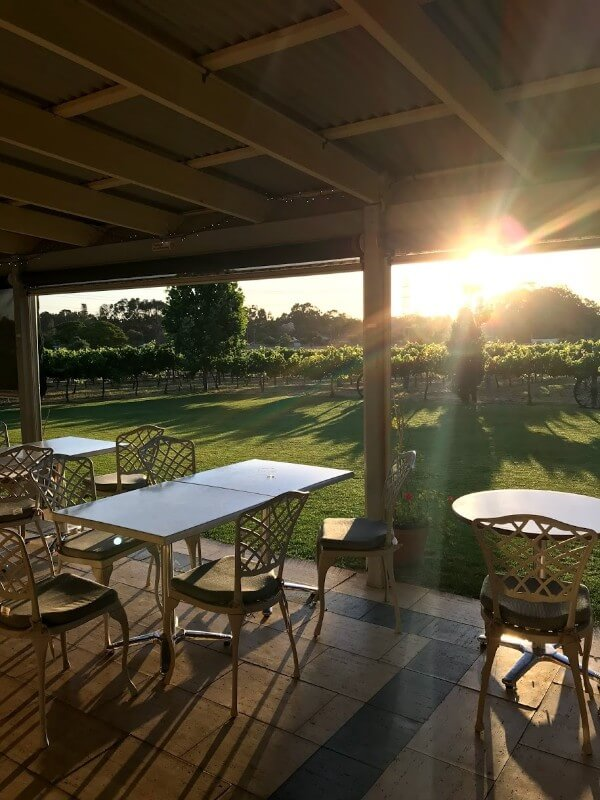 table-and-chairs-on-a-verandah-at-pinelli-estate-winery-restaurant-looking-at-the-sunset