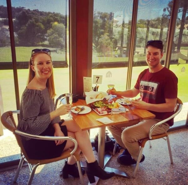naomi and bryce sitting at a table drinking wine at st aiden winery