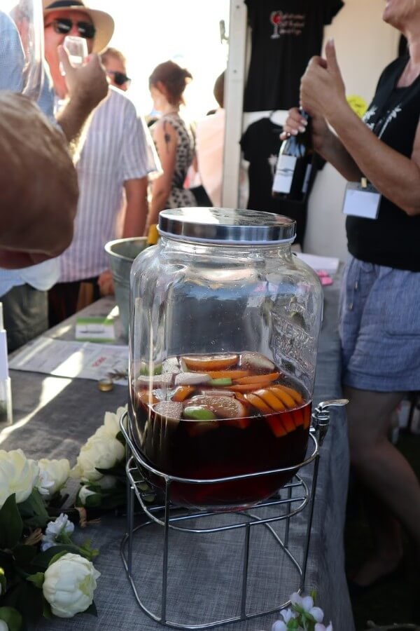 red sangria and fruit in a container on stand