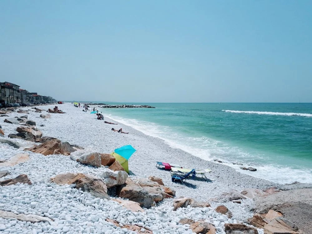 a beach with white pebbles, turquoise sea and a few people sunbathing. marine di Pisa, Italy.