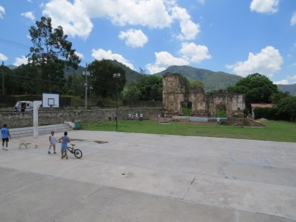 Kids playing in front of a ruin under restoration. Such a contrast.