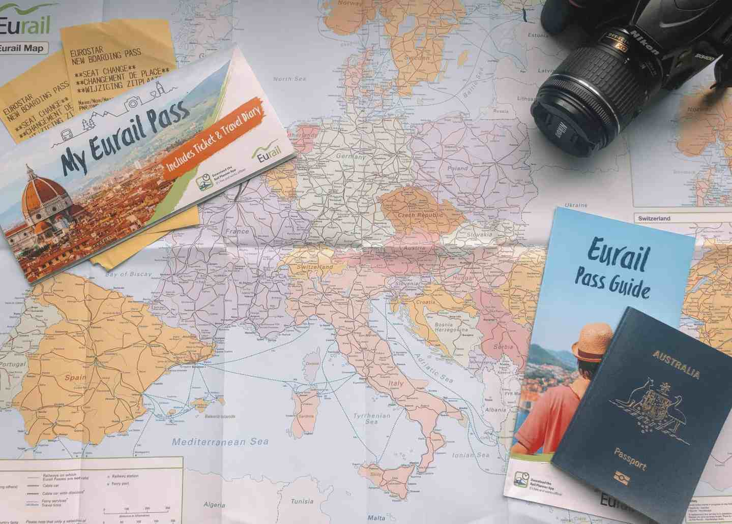 The Eurail Pass Guide, Eurail Pass, Australian Passport and Camera sitting on a Eurail Map
