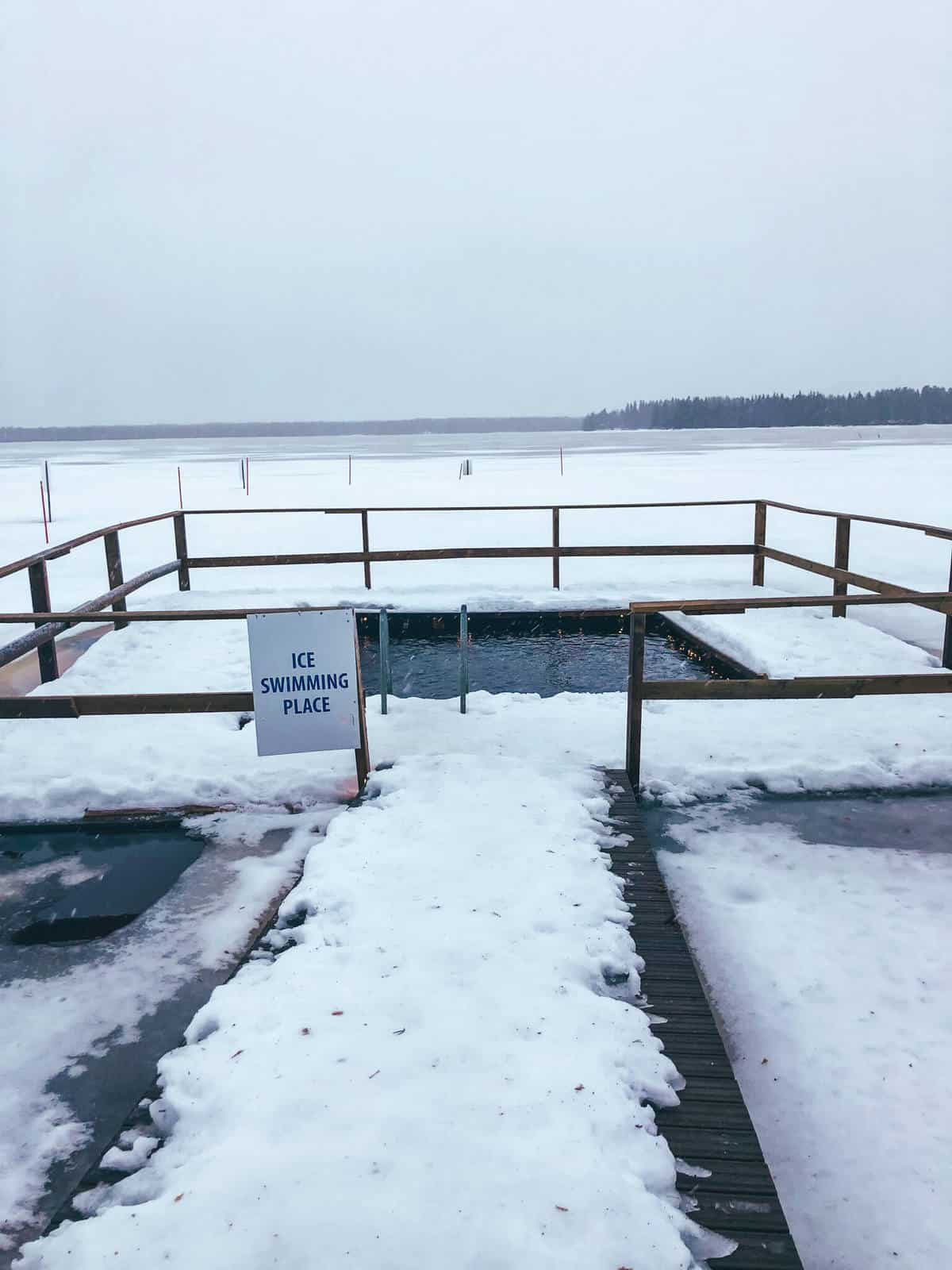 An ice swimming place in front of a frozen lake surrounded by snow