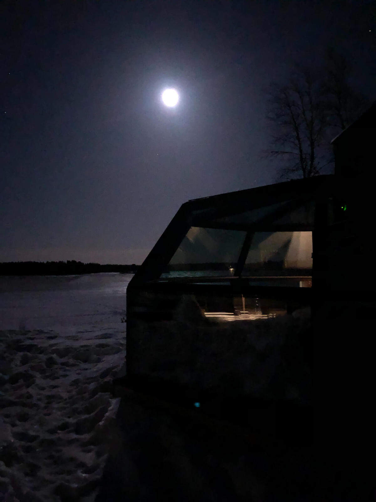 The moon rising over a glass igloo in front of a frozen lake surrounded by snow