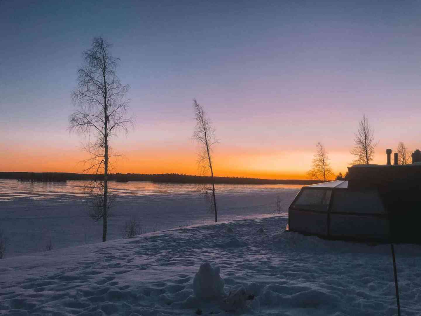 Sunset over a glass igloo on the side of tree lined frozen lake