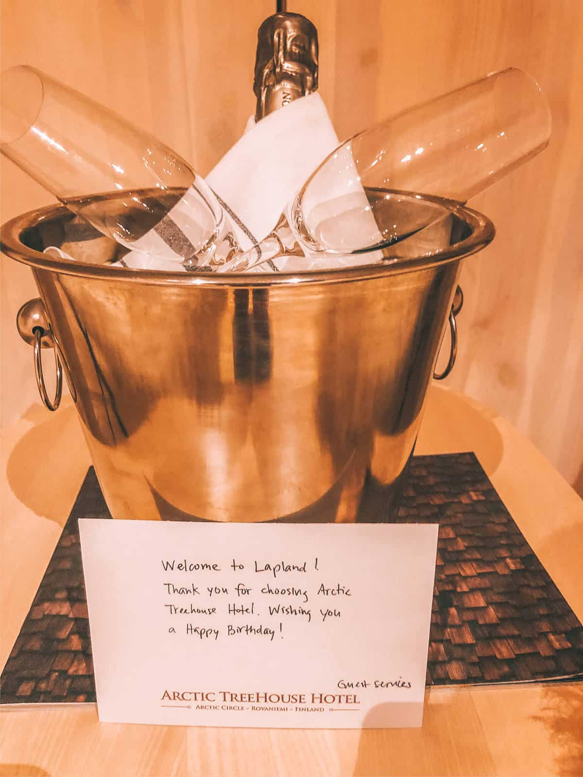 A wine cooler with a bottle of wine and two glasses. A note read Welcome to Lapland! Thank you for choosing Arctic Treehouse Hotel. Wish you a Happy Birthday!