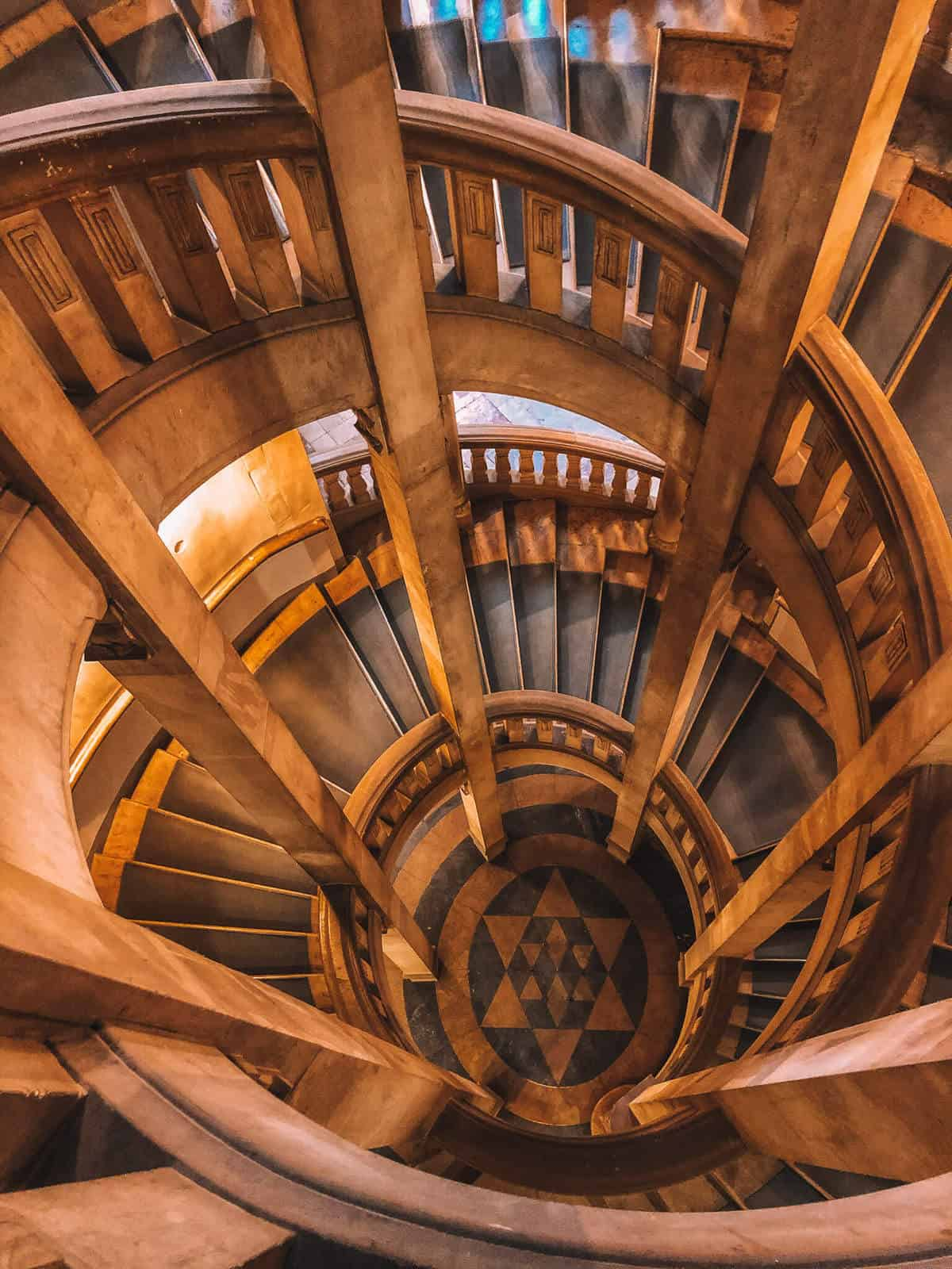 A spiral stair case leading down to a floor with a star tiled into the floor