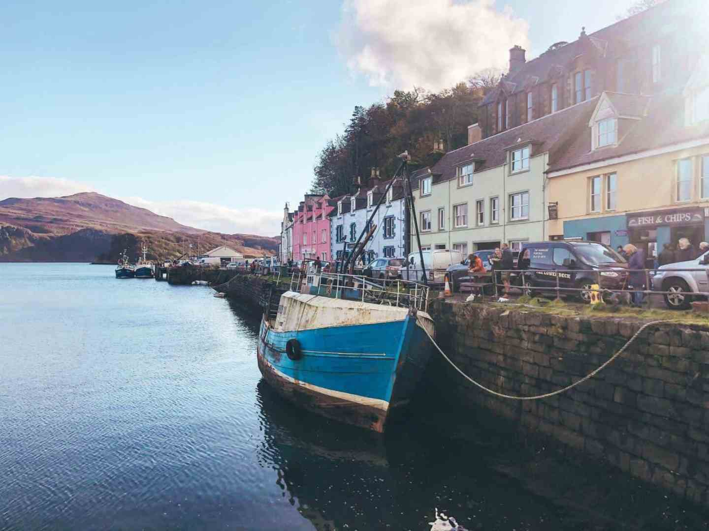 Colourful houses on the edge of a harbour with an old boat tired to the side and mountains in the background