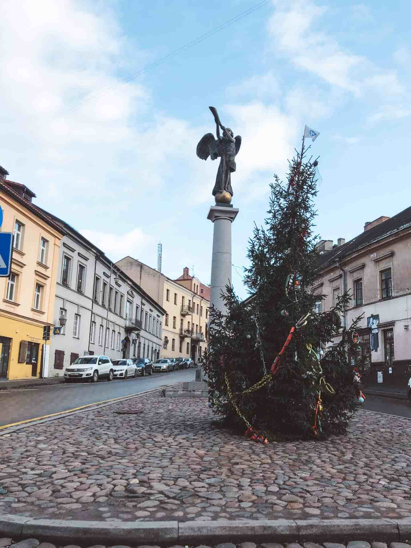 A Christmas tree in front of a pole with an angel on top in a city street