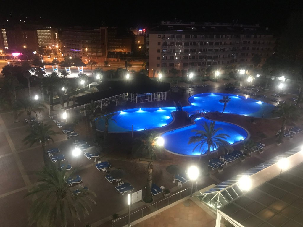 View of the pool area and beyond at night at Costa Encantada lloret de mar
