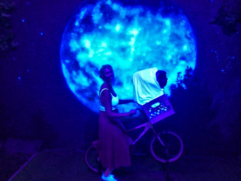 Nicola on ET's bike in front of a moon at Madame Tussauds Blackpool