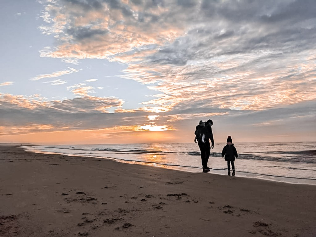 Neil, felix and Dexter walking towards the sea with the sun setting on Ainsdale beach