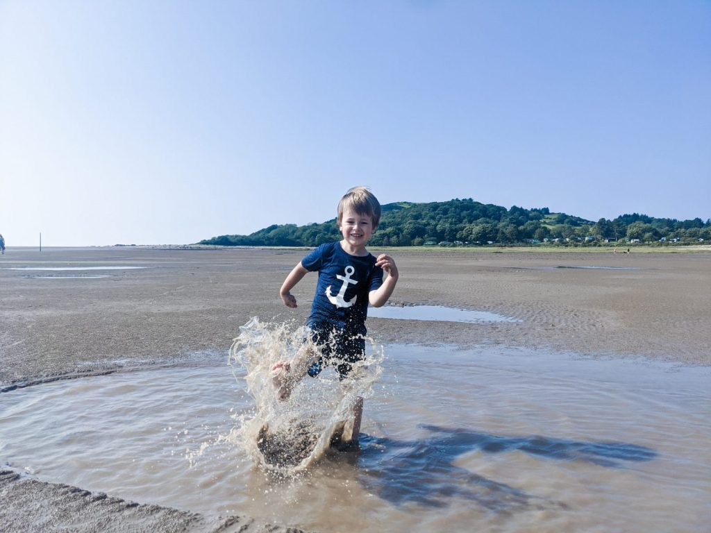 Dexter splashing a small pool of water at Sandyhills beach
