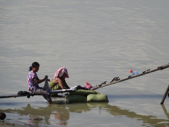Locals doing laundry by the river. Bagan, Myanmar