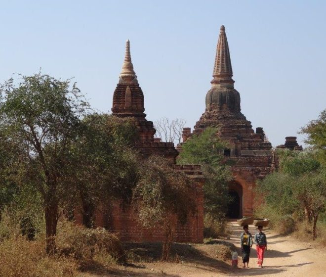 Locals strolling past on their way to their daily routines. Bagan, Myanmar