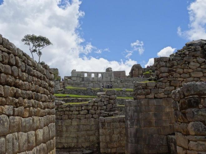 Contrasts. Regular houses and temple at Machu Picchu, Peru