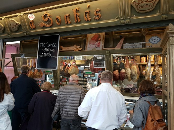 Standing in line for the cold cuts of Mangalica. Taste Hungary food tour. Budapest, Hungary.