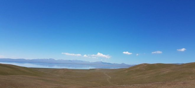The beautiful Song Kul lake reflecting the mountains. Three day horse-riding trip to Song Kul, Kyrgyzstan.