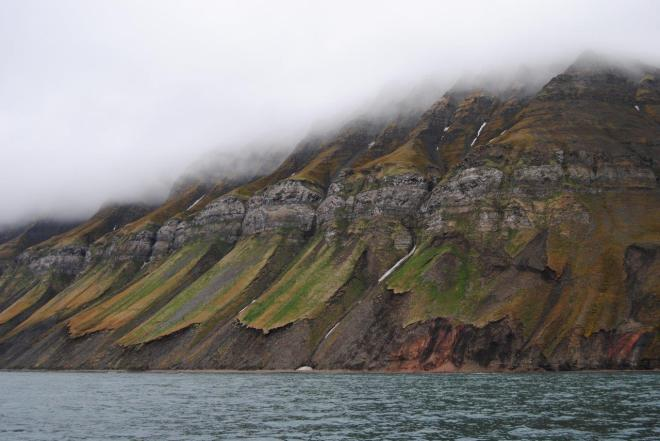 The fog is hanging low down the mountainside. Svalbard, Norway.
