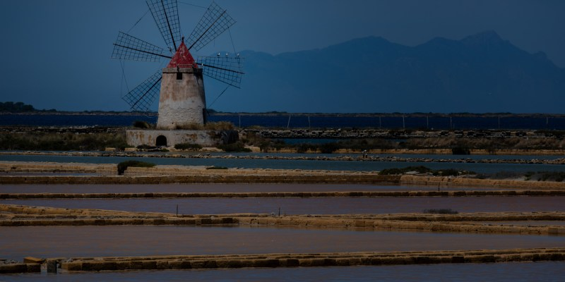 For centuries the typical Sicilian windmills have worked to move the water around the saltpans in the Saline della Laguna near Marsala, Sicily. Nowadays replaced by modern waterpumps, they are very photogenic surrounded by the water basins of different shades of blue and pink caused by the salinity of the brine. This location is included in the 2019 and 2020 itineraries of the Western Sicily and Sicily Highlights Phototours by Focus on Sicilia.