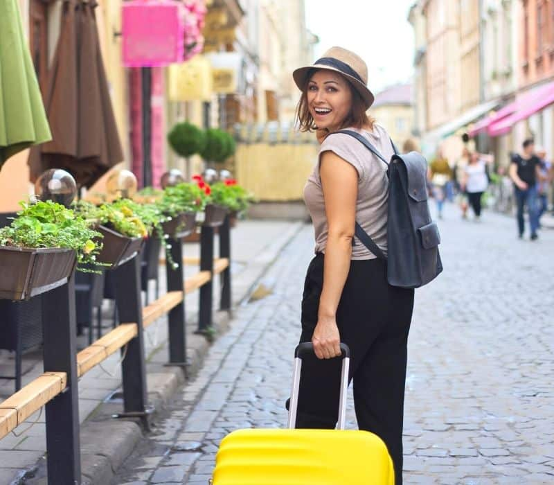 Woman happy pulling her yellow suitcase through town
