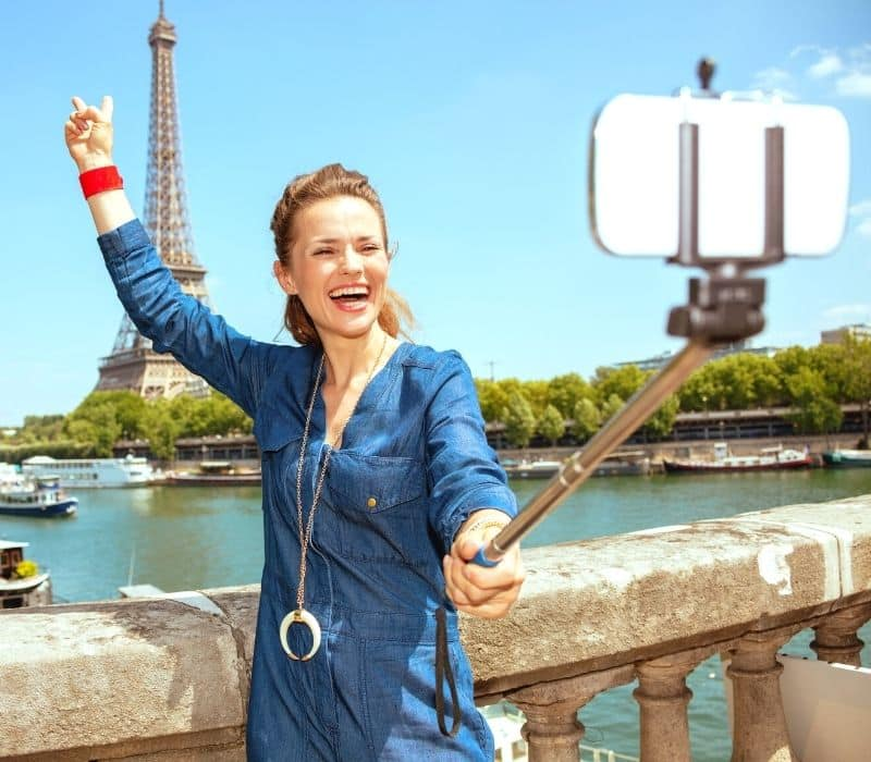 Woman with a selfie stick taking a photo in Paris