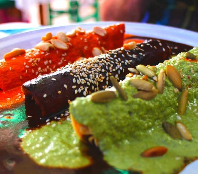 red, black and green mole enchiladas in oaxaca mexico - Traveling to Oaxaca