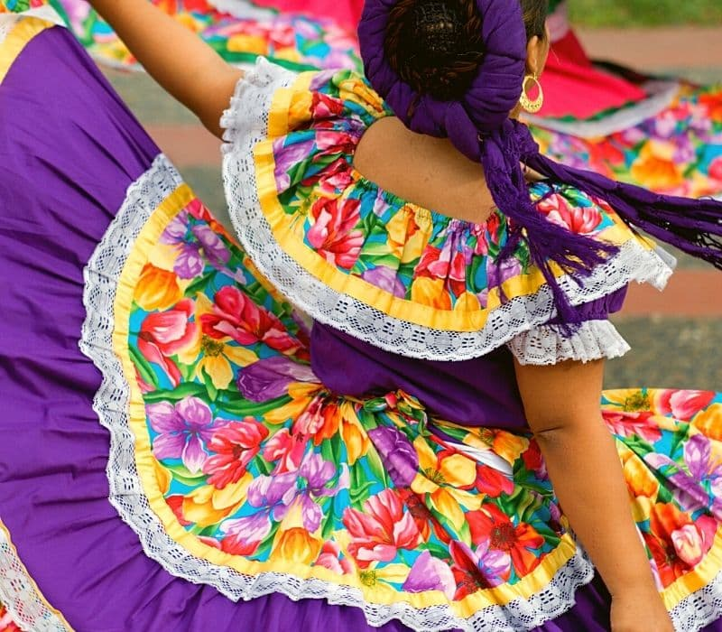 Woman in traditional Mexican dress doing a dance - Traveling to Oaxaca