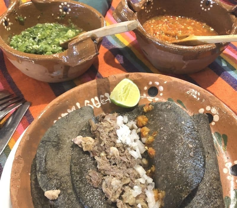tacos with blue corn tortillas and red and green salsas