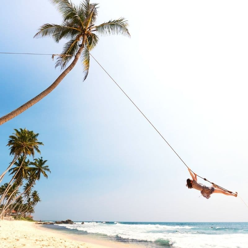Happy woman on a beach tree swing