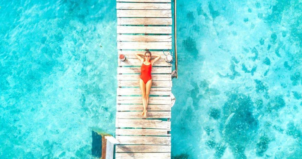 woman in a red swimsuit laying on a dock at Bacalar Lagoon